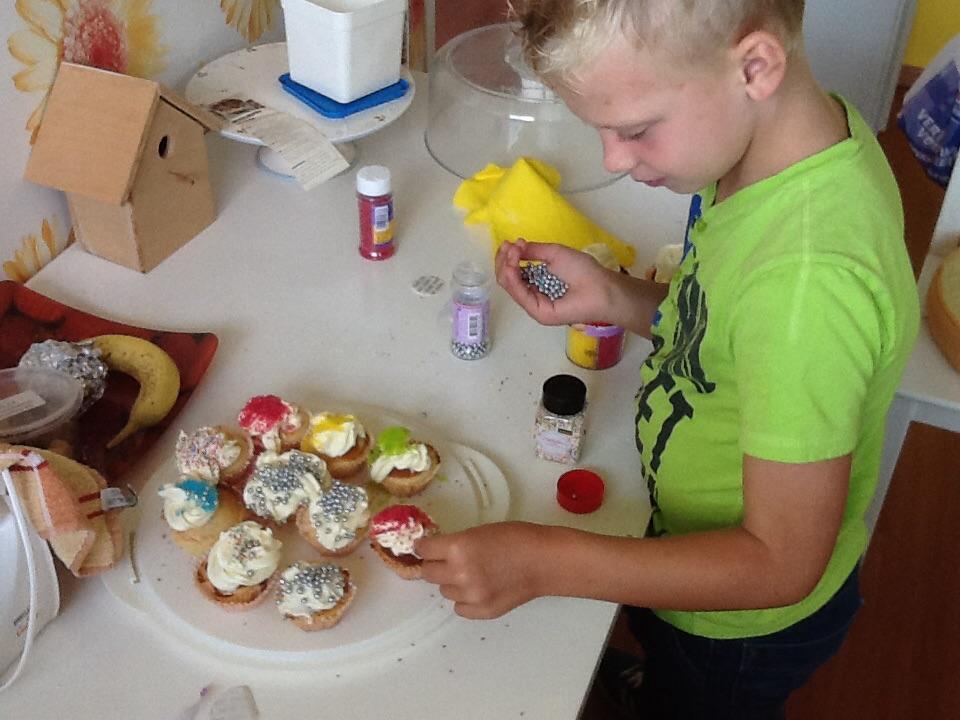 jongetje versiert cupcakes met slagroom en snoep