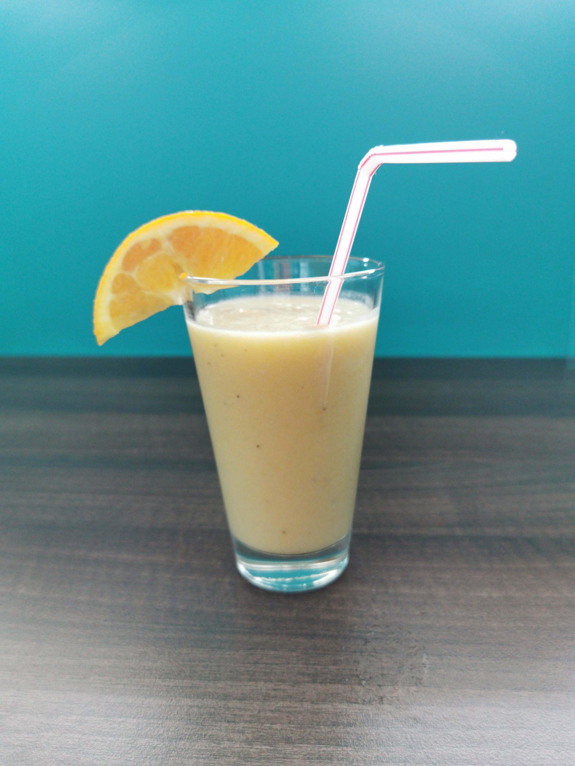 smoothie van banaan en kokos in een glas met een rietje