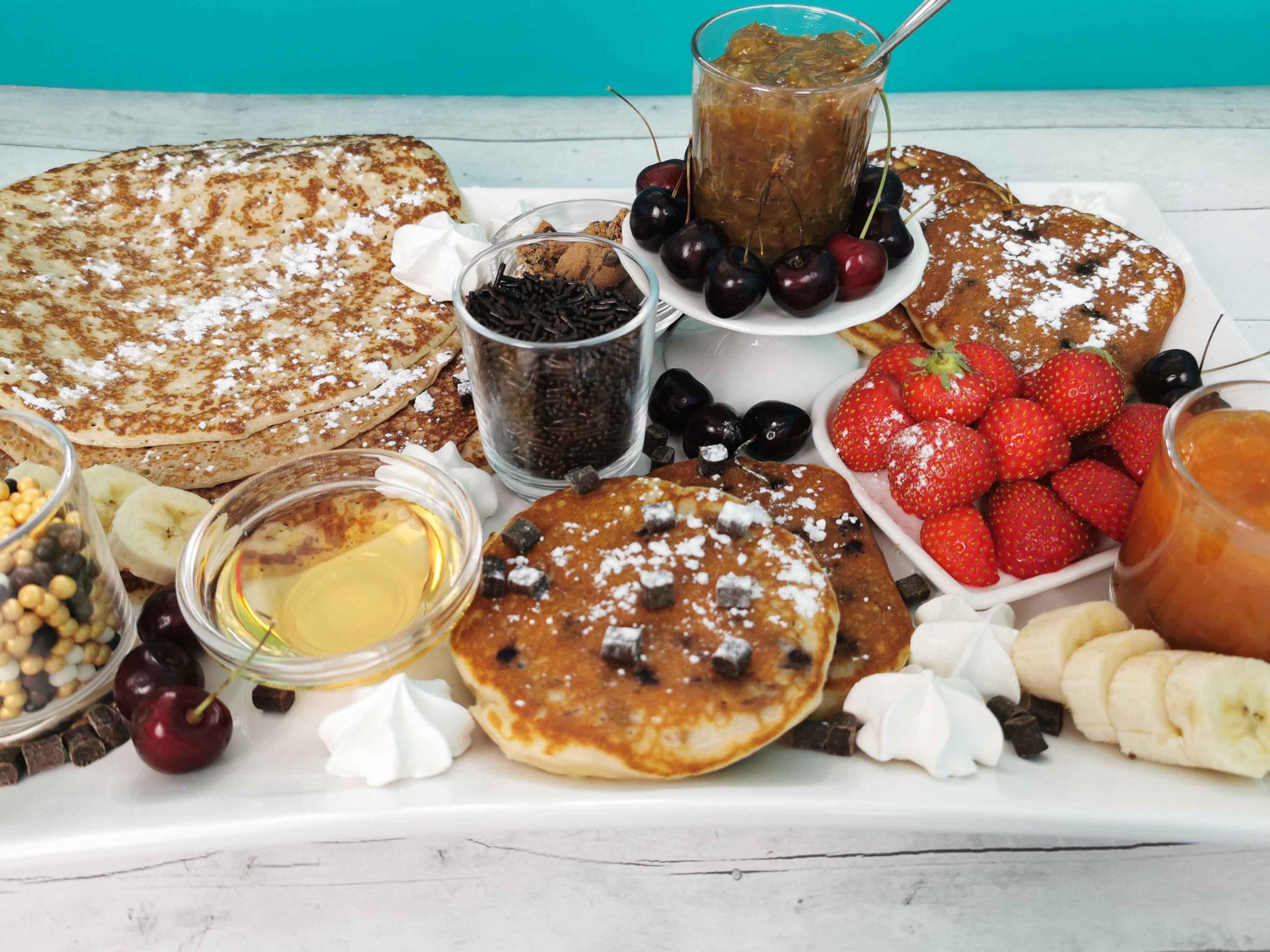 een schaal met pannenkoeken, jam, fruit en zoetigheden