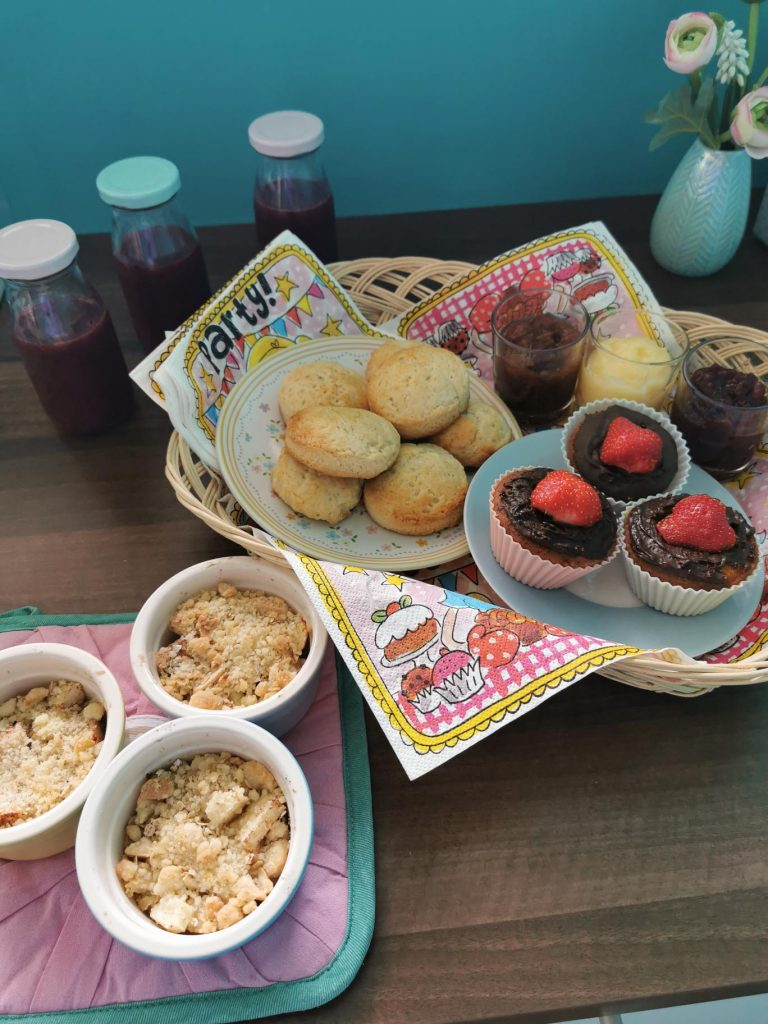 high tea met scones en cupcakes in een mandje en verse sapjes