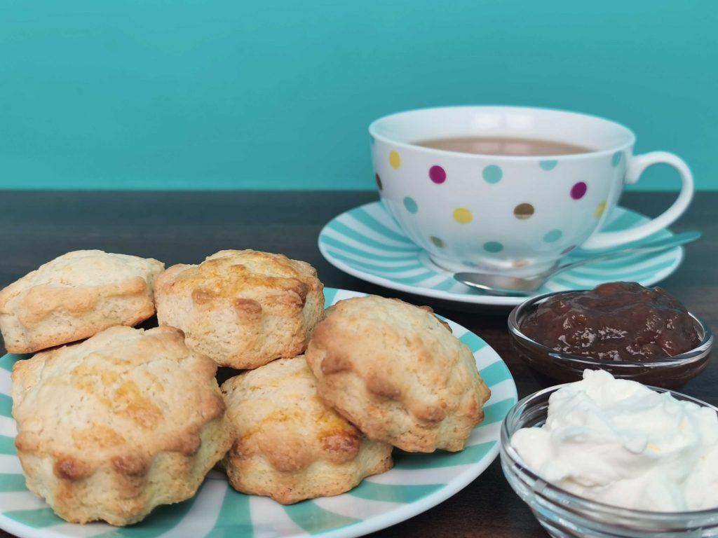 stapeltje scones met jam, slagroom en een kop thee