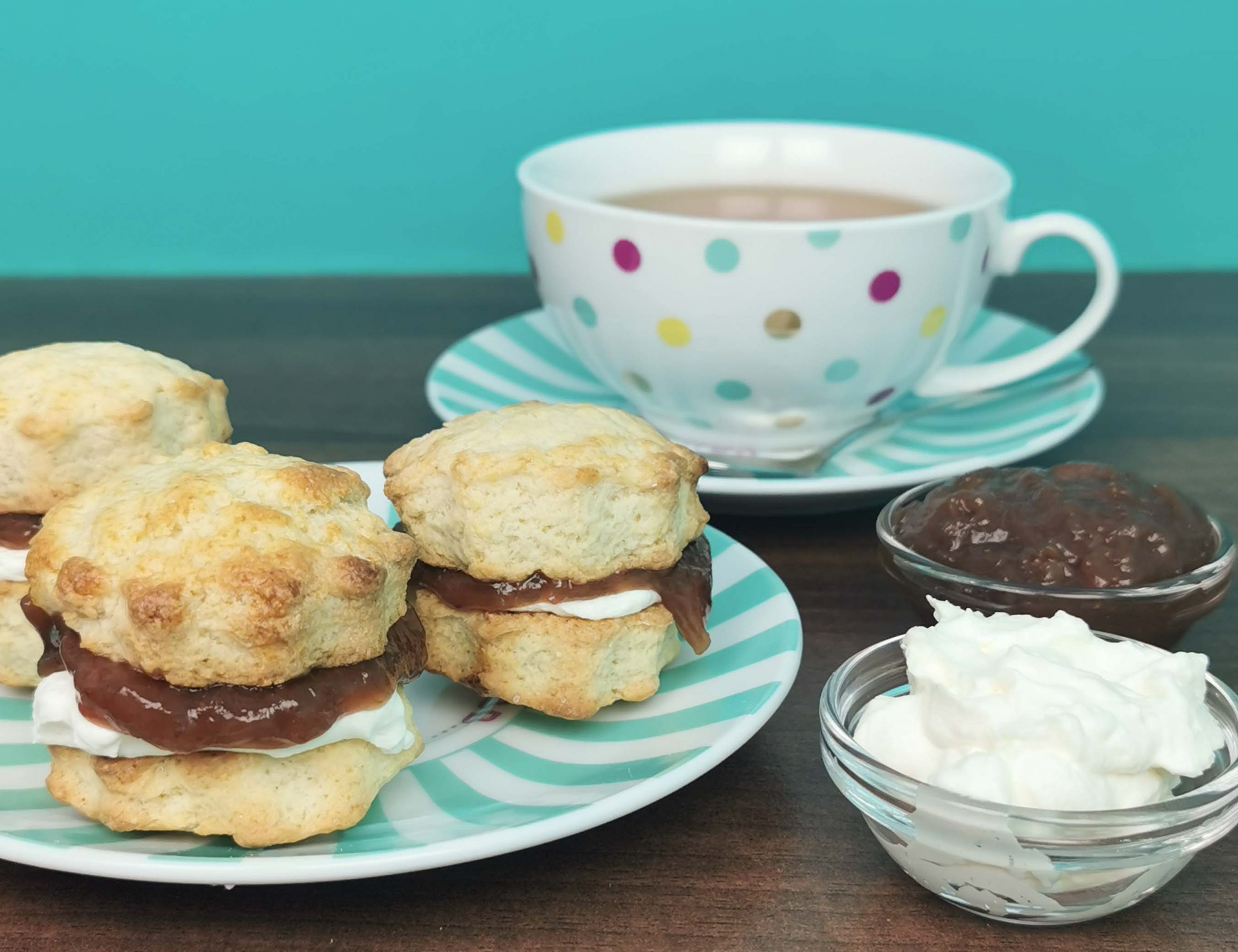 3 scones, een kop thee en bakjes met room en jam