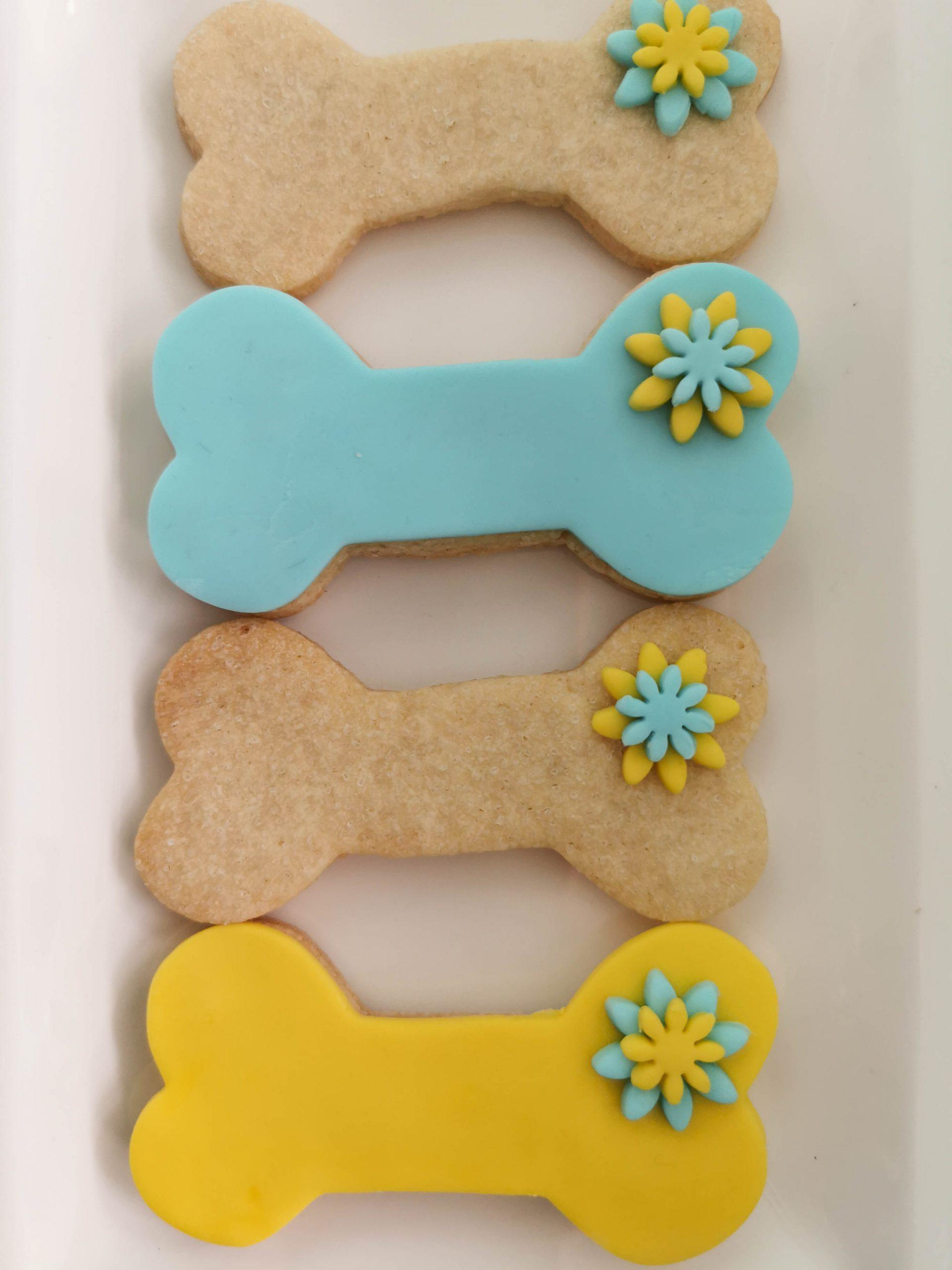 4 koekjes in de vorm van een botje, waarvan er 2 gedecoreerd zijn met fondant